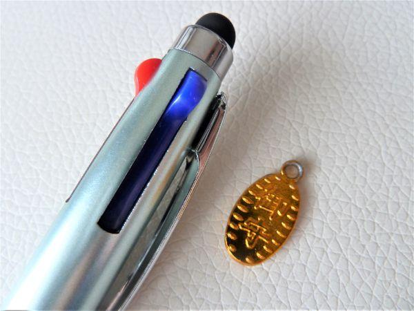 金のお守りコインとボールペン